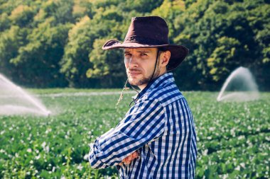 Farmer stands on the field on the watering or sprinkler system background. A young agronomist is on a plantation and checks quality of the harvest.