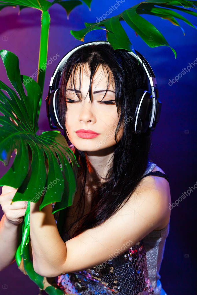 Brunette girl on tropical leaves background. DJ woman plays music disko party on the equipment in the summer club.