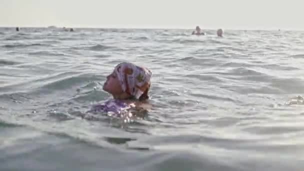 Little young girl learning to swim in the sea