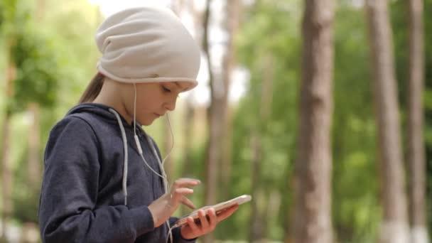 Dítě používá mobilní telefon. Dítě se dívá na obrazovku zařízení.