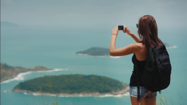 woman with a backpack takes photos on the phone on a trip