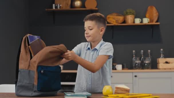 Boldog tanuló hozza egy hátizsák tankönyvek, füzet, ebéd. Vissza az iskolába