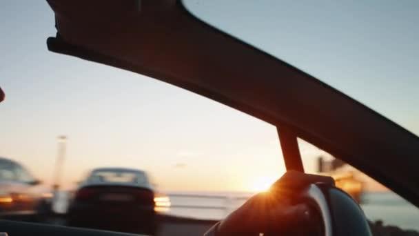 ruce na volantu při západu slunce