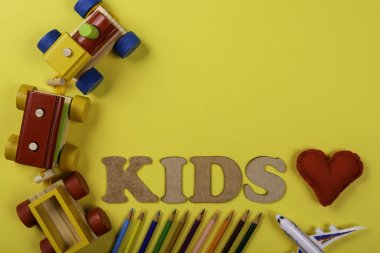 Colorful wooden train on yellow background and various colored pencils and with text written kids and red fabric heart.