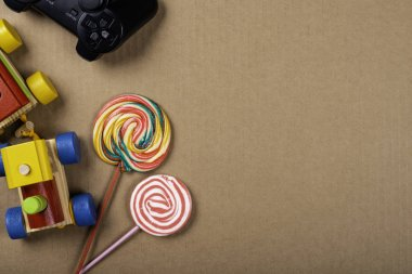 Children's Day. Wooden train, lollipop and video game control over brown background. Copy space.