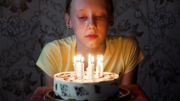 giovane ragazza che spegne le candeline di compleanno