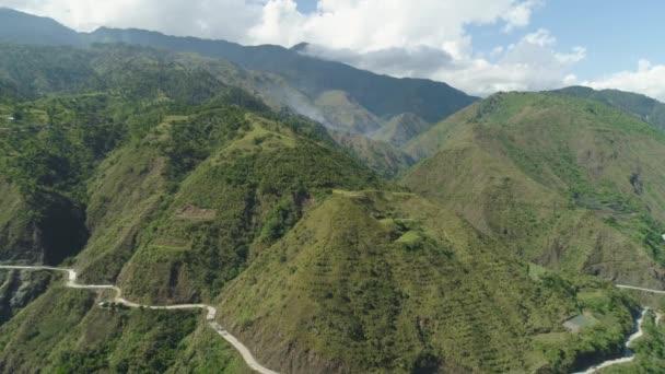 Horská křivka je cesta po svazích hor a kopců pokryté zeleným lesem a vegetací. Filipíny, Luzon