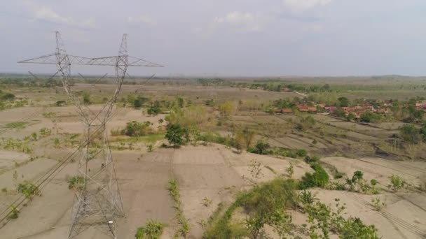 Electricity pylons bearing power supply across rural landscape. aerial view power pylons and high voltage lines java, indonesia.High voltage metal post, tower. Electric Power Transmission Lines over