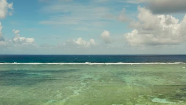 Vlny se rozbíjejí na korálovém útesu.