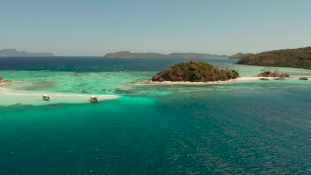 Malý ostrov torpic s bílou písečnou pláží, pohled shora.
