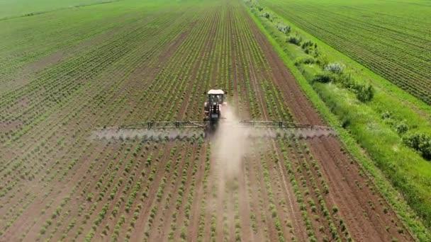 Traktor rozprašuje pesticidy na rostlinném poli rozprašovačem