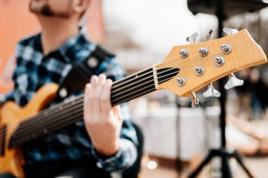 Photo of musician playng on six string fretless bass guitar on the street in front of people.