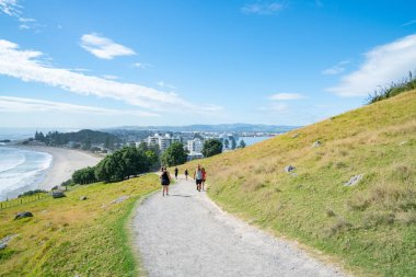 People outdoors taking morning walk up slope Mount Maunganui