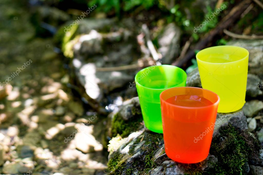 three colorful cups near a spring with water in the summer in nature