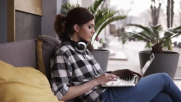 Mladá koncentrované žena, sedí v místnosti nebo v prostoru se systémem windows. Práce na notebooku na její nohy a sluchátka kolem krku. Moderní, světlý prostor. Boční pohled