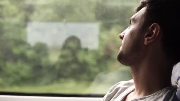 Profil a szép sötét hajú ember elgondolkozva nézte az ablakot. Vonattal utazik. Nézi a kamera. Izgatott az utazás. Mosolyogva. Oldalnézet
