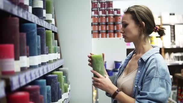 Boční pohled atraktivní ženy výběr různé barevné svíčky od regál v supermarketu. Vůně zelená svíčka z poličky