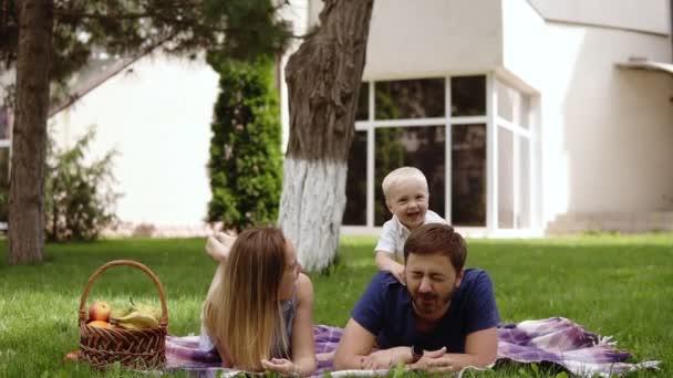 Šťastný radostné mladých rodina otec, matka a malý syn venku bavit, hrát spolu v létě parku, venkov. Maminka, Tatínek a syn na otci zpět junping a směje se. Bílý dům na