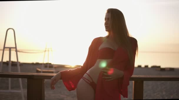 Blonde, attractive woman in red swimsuit and red dressing gown leaning on a wooden railing near the sea. Morning sunrise. Sunlight