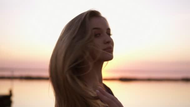 Krásu módní portrét blondýnka s dlouhými vlasy a krásné Nahé rty. Módní portrét. Usměvavá blondýnka v módní vzhled. Moře na ranní soumrak pozadí