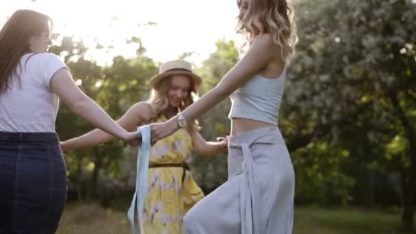 Cheerful girlfriends having fun together outdoors. Round dance, holding hands. Bright, sunny day. Slow motion