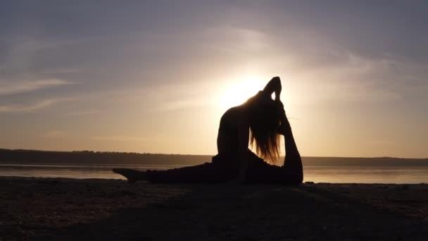 Mladá krásná žena nosí sportovní oblečení jógu cvičit proti moři, dělám jógu nebo pilates cvičení. Variace z opičího boha, rozdělení, hanumanasana s backbend. Plná délka
