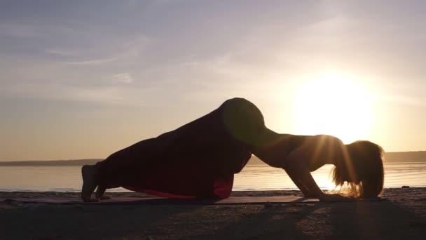 Krásné záběry na západ slunce na pláži, Žena, která dělá jógu asana na rohoži, backbend, Urdhva Mukha Shvansana. Zpomalený pohyb