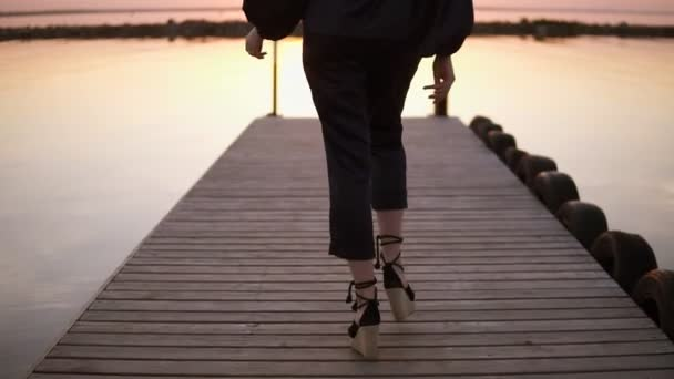 Tracking backside footage of a tall, long haired woman walking in black clothes by the pier. Clothes model. Sunlight, morning