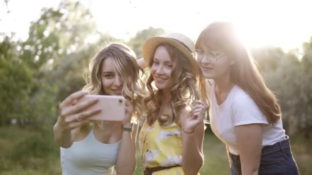 Group of three beautiful girls friends making picnic outdoor. They take selfie photo from smartphone. Sun shines on the background
