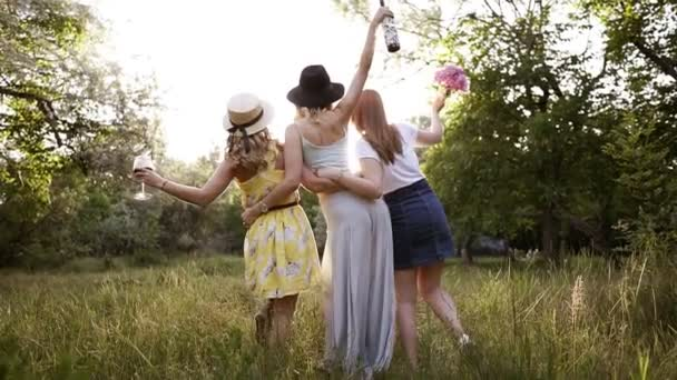 Rare view of a group of three young nice girls embrace themselves looking at perspective. Girl in the middle is holding a wine bottle. Green meadow