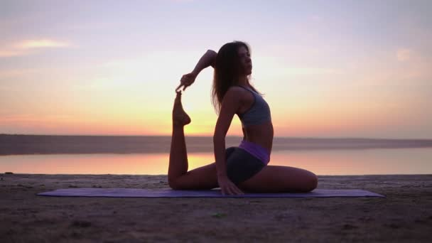 Attractive yogi woman exercising on a mat near the sea. Mix ofyoga postures. Morning dusk