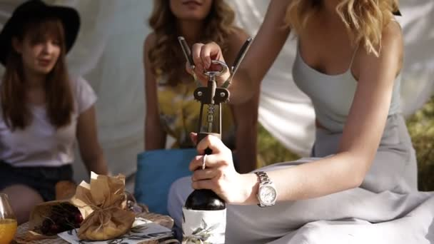 Women on a picnic with two her girlfriends. sitting on a plaid. Aim footage of process of opening wine bottle. Hen party