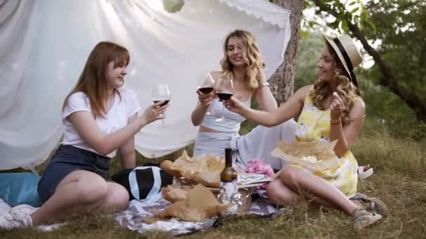 Hen party outdoors. Three pretty woman have a picnic, sitting on the plaid, drinking red wine. Cheers. White sheet hanging on a trees