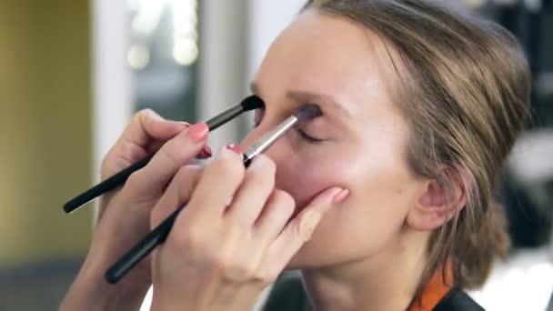 Profesionální vizážistka dělá make-up pro mladé roztomilé modelu. Umělec uvedení oči stínů pomocí dvou kartáčů a dělá to dohromady. Detailní záběr
