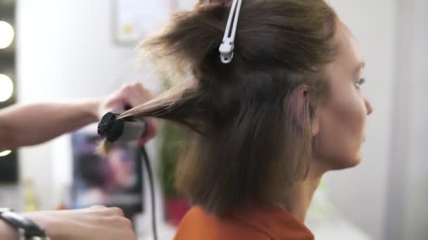 Kadeřník narovnává vlasy Sedící žena s vlasy železa v kosmetické studio. Ona drží zvláštní zařízení v rukou a jemně pohybuje přes krátké blond vlasy od shora dolů