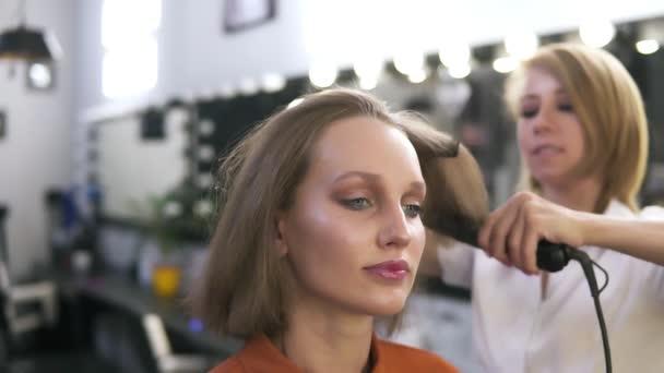 Atraktivní kavkazský dívky s tvoří v salonu krásy. Kadeřník narovnává vlasy žehličkou. Rozmazané pozadí - bílá lampy a zrcadla