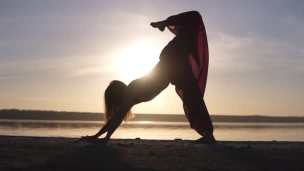 One caucasian woman exercising yoga outdoors. Silhouette isolated on a sunset and sea on the background