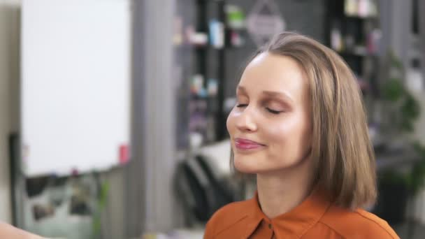 A blonde is sitting on the chair and a make up artist is fihishing her visage with a face spray. Her make up is already finished. Salon. Slow motion