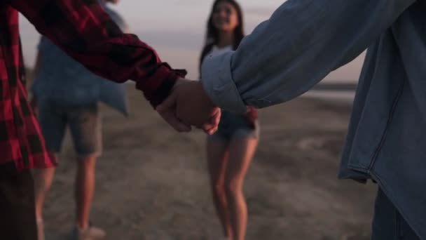 Close up footage of a couple holding hands together while walking on the beach. Another couple on a perspective. Young people having fun together. Dusk