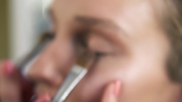 The make-up artist puts light shiny eyeshadow on a models eyelids using two professional brushes. Close up. Make up process