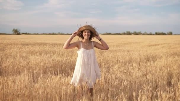 Krásná bruneta kudrnaté dáma v pšeničné pole v létě. Usmíval se a pózuje v slaměný klobouk. Pohled zepředu