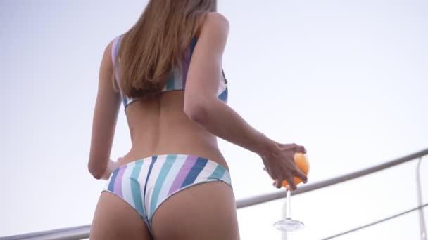 Alacsony szögből készült felvételeket a háton és a csábító, szexi nő a bikini narancs koktél pohár emeletre. Nappali, tengerparti, nyáron