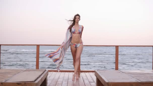 Slow motion footage of a beautiful model in bikini and silk summer gown walk by wooden floor with sea on the background. Wind blowing, summertime