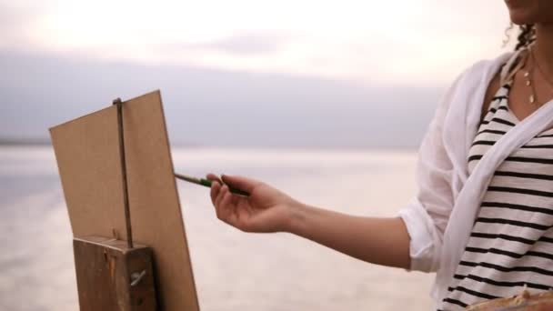Close up of an artists art process. An easel and palette. Girl is putting some color paints on canvas. Blurred lake surround on the background