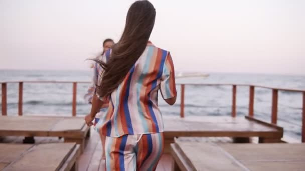 Front view of a gorgeous long legged tanned women walking by wooden seaside area. Dressed in clothes in the same style - sil colorful summer clothes. Windy, summer, daytime