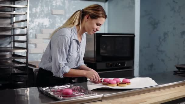 Young smiling woman in blue shirt and black apron on a final stage of preparing french dessert - putting pink glazed cake in tartles. Modern kitchen. Bakery, pastry, culinary concept