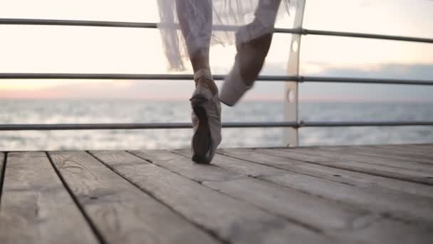 Close up of a ballet dancers feet as she practices point exercises. Ballerina elegantly walks by the embankment in white pointe. Slow motion