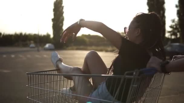 Happy young friends with shopping cart in a parking lot near a supermarket. Man pushing cart with the girl inside. Tracking footage