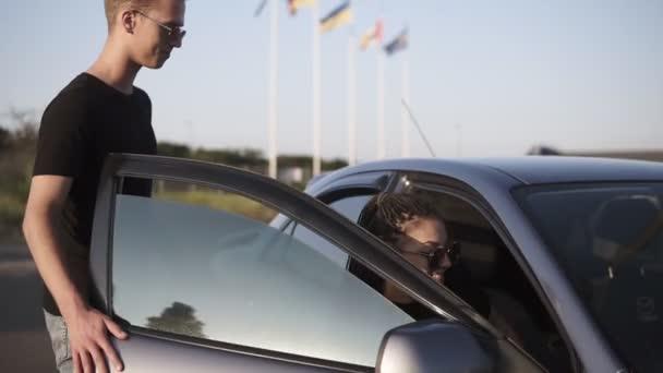 Filmaufnahmen eines jungen Menschen - Mann und Frau steigen ins Auto. Mann öffnet Autotür für Freundin und setzt sich dann auf den Fahrersitz eines dunkelsilberfarbenen Autos tagsüber