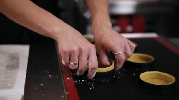 Female hands of professional confectioner forming dough for baking tartlets. Black working surface. Indoors, culinary master class